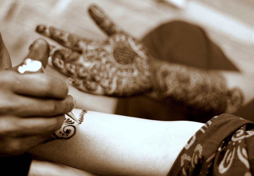 The photo shows a woman's hands being covered in intricate henna designs.