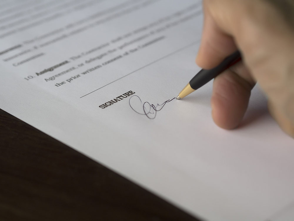 A photo shows someone signing a contract.