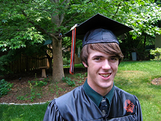 A photo shows a smiling person wearing a graduation cap and gown.