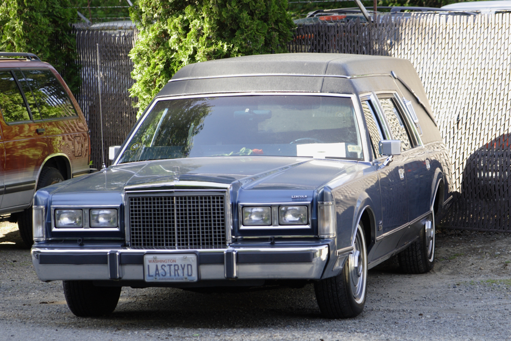 "A hearse with the license plate ""LASTRYD"" is shown here."