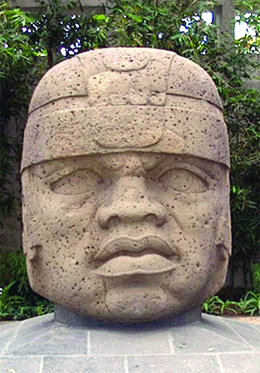 A photograph shows a massive carved stone head with a flat nose, large lips, and slightly crossed eyes.
