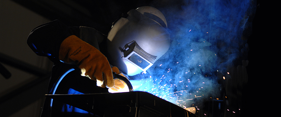 Sparks fly as a welder wearing a mask welds.