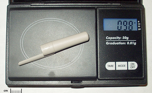 A plastic pen cap is sitting on a digital scale and has a measured mass of 0.98 grams.