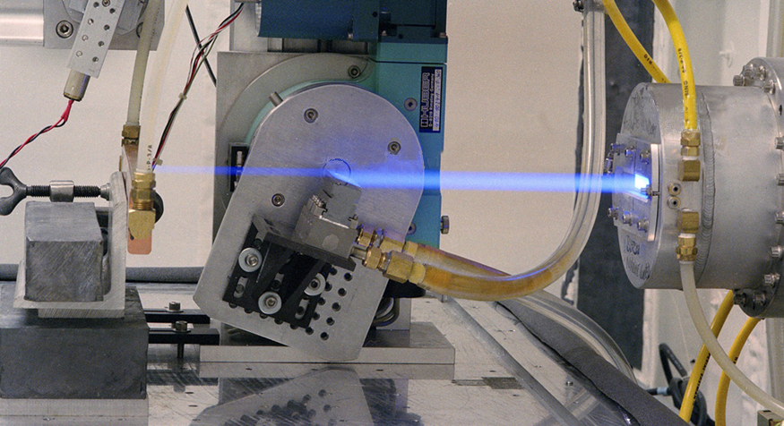 The image shows a ray of blue light being emitted from a small slit in a cylindrical source.