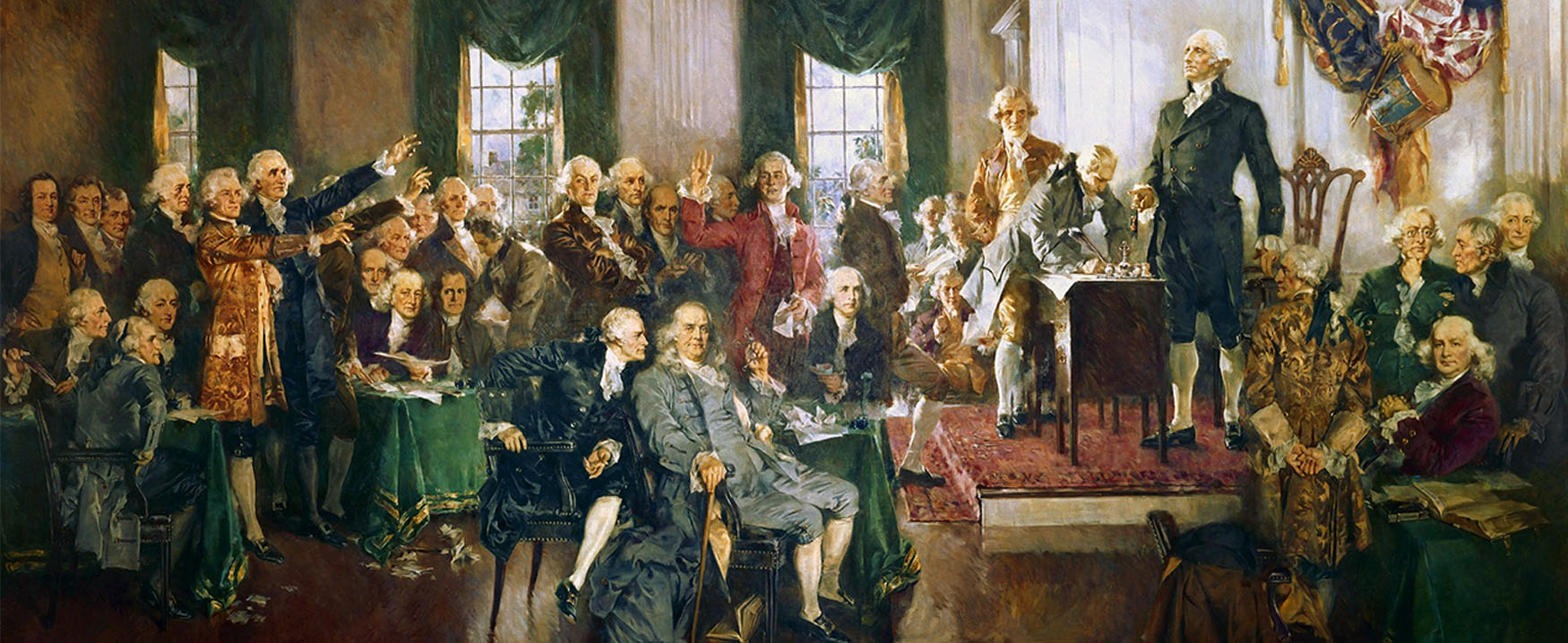 The image displays Howard Chandler Christy's painting, titled Signing of the Constitution.  The painting depicts forty people seated or standing around a room in what is now known as Independence Hall.  Featured are George Washington, Benjamin Franklin, Alexander Hamilton, and James Madison.  In the moment captured by the artist, delegate Richard Spaight of North Carolina signs the Constitution.