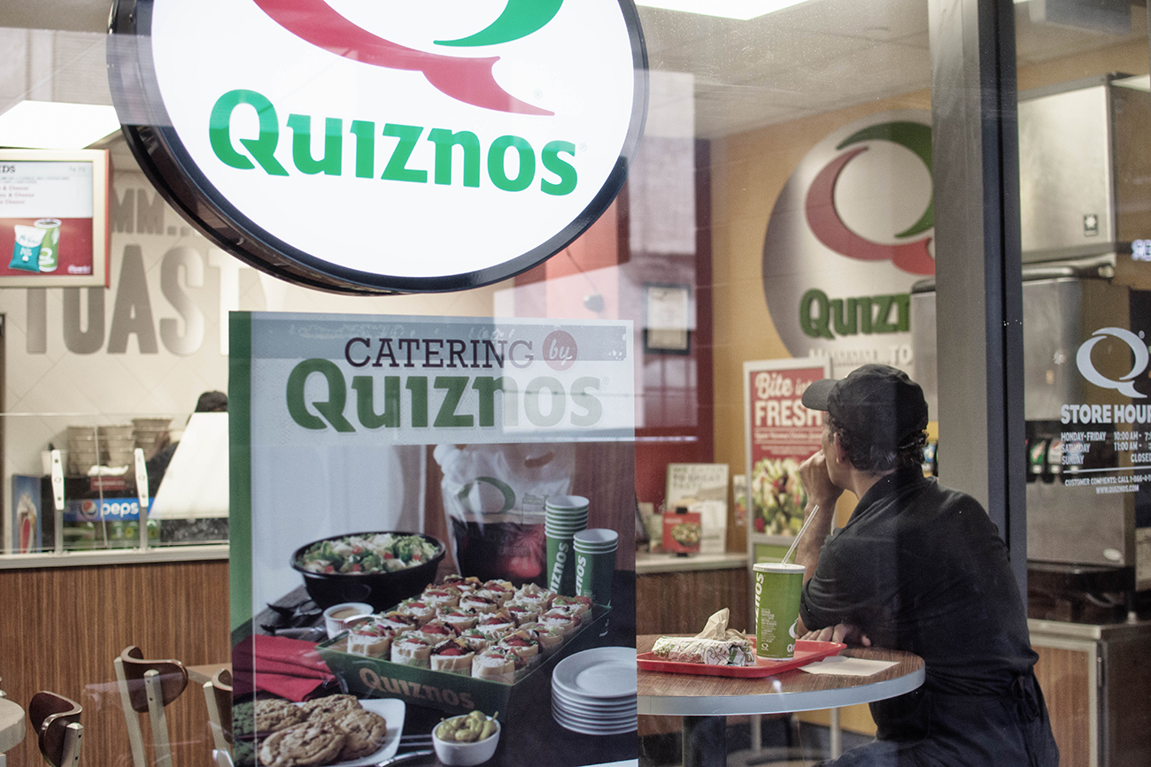 A photograph shows inside of a small Quiznos restaurant.