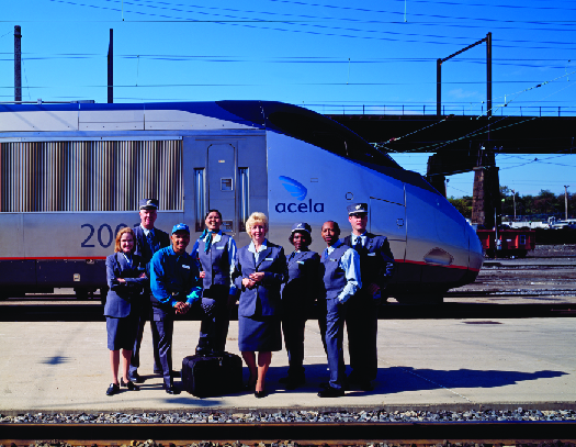 A photo of Amtrak staff standing on a train platform as a train passes behind them.