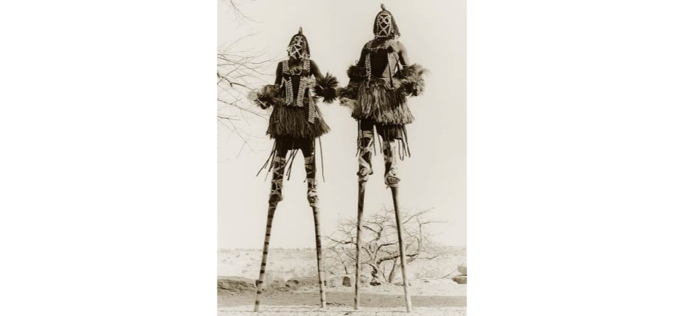 Picture shows a photograph of two stilt walkers in standing position.