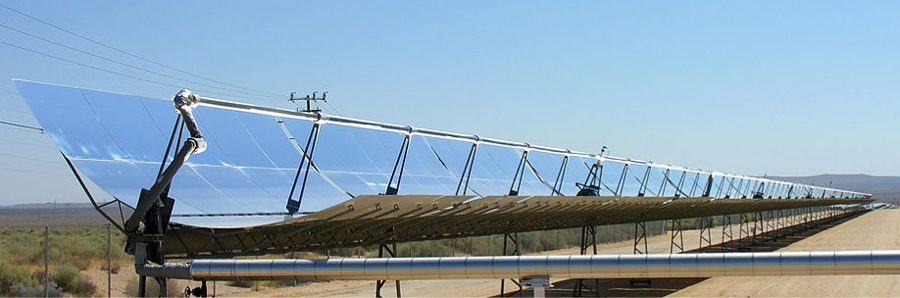 Photograph of several parabolic trough collectors set in a row in an open area.