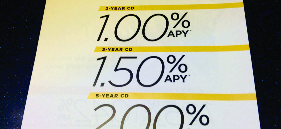 "This image shows a sign at a bank indicating annual percentage rates for CDs. The top line says ""Earn big with a locked-in rate"". The second line reads 2-year CD with one percent annual percentage rate; the third line reads 3-year CD with a 1.5 percent  annual percentage rate, and the fourth line reads 5-year CD with a 2 percent annual percentage rate."