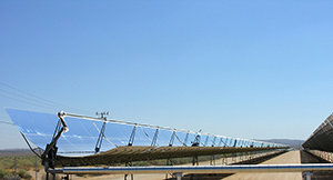 This photo depicts a long length of parabolic trough deflectors angled toward the sun.