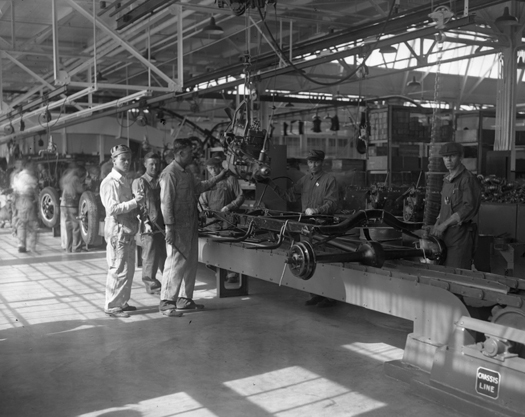 An image of a few people standing in an automotive plant next to some machinery.