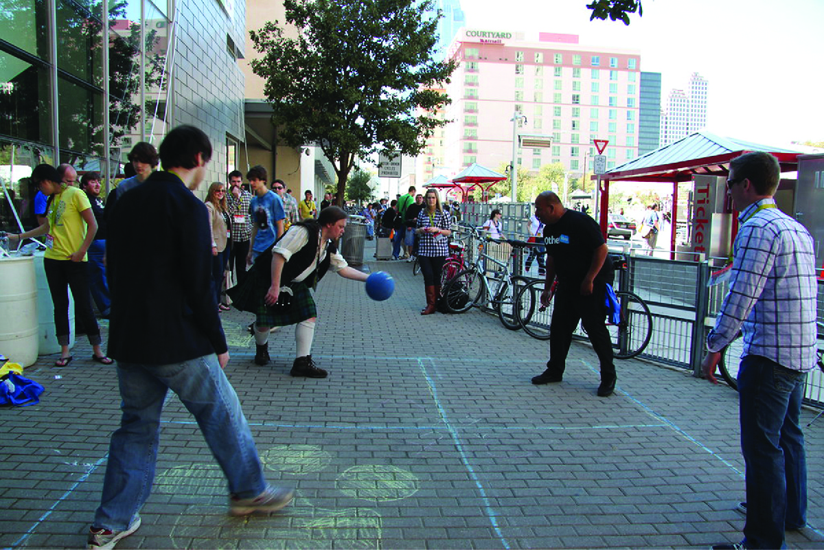 People playing a game of foursquare on a brick sidewalk.