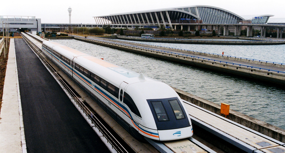A photograph shows a maglev train traveling past an airport.
