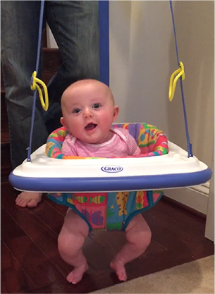 A photo of a baby in a hanging bouncer.