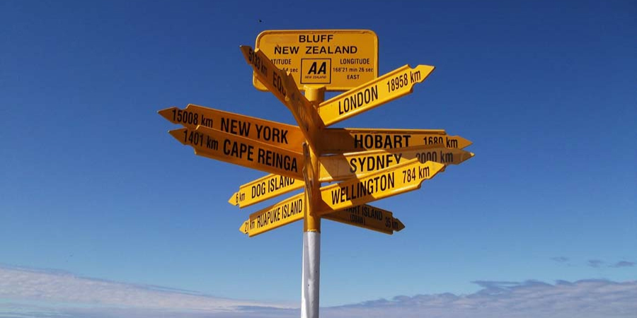 A photograph of a signpost with distances to numerous locations in different directions.