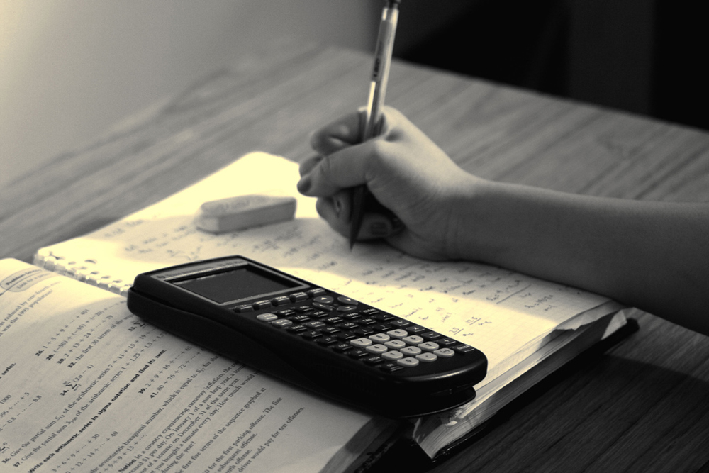 Close-up photo of a hand writing in a notebook. On top of the notebook is a graphing calculator.