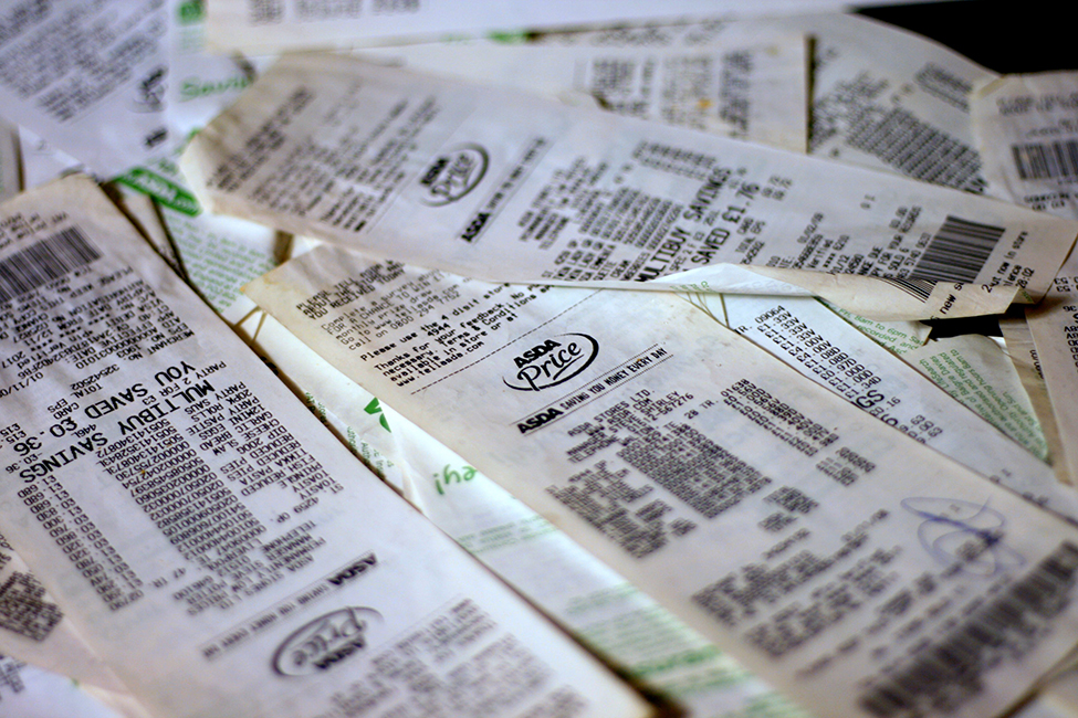 This is a photo of a pile of grocery store receipts. The items and prices are blurred.