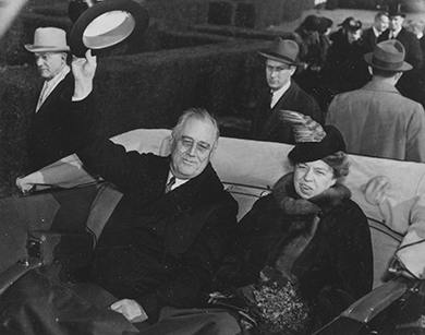 A photograph shows Franklin and Eleanor Roosevelt smiling as they ride in the back of a coach. Franklin Roosevelt waves his hat at onlookers.