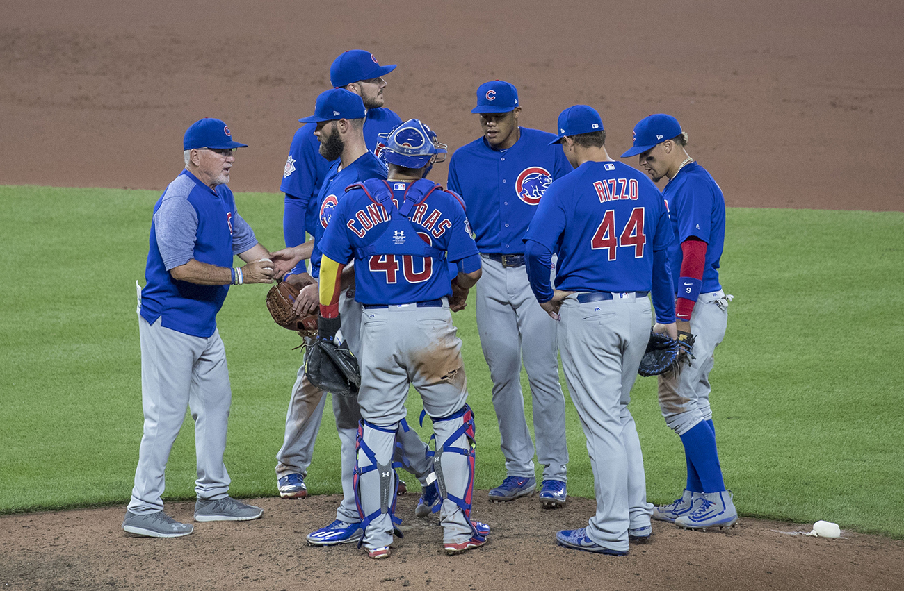 A photo shows Joe Madden, manager of the Chicago Cubs baseball team at pitcher mound, talking to the team.