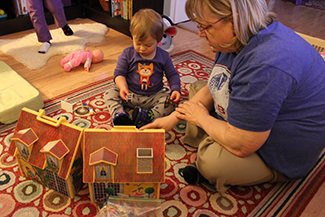 An adult and a small child are depicted sitting on a rug next to a toy house.