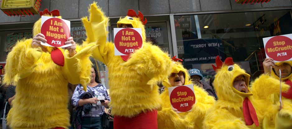 "Protesters are shown here wearing yellow chicken costumers and holding PETA signs that say ""I Am Not a Nugget"" and ""Stop McCruelty."""