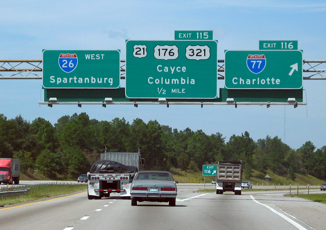 A photograph shows a highway with large signs that signal Spartanburg is on Interstate 26 west, and Charlotte in on Interstate 77.