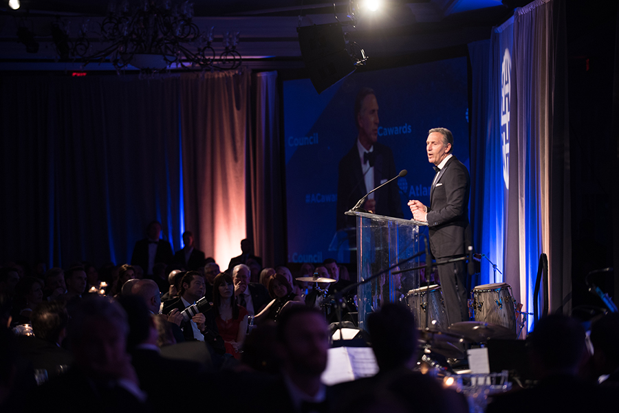 A photo shows Howard Schultz delivering a speech after receiving Distinguished Business Leadership Award.