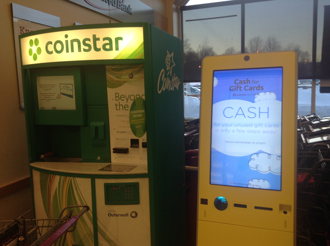 Photograph shows a coin star machine beside a cash for gift cards machine.