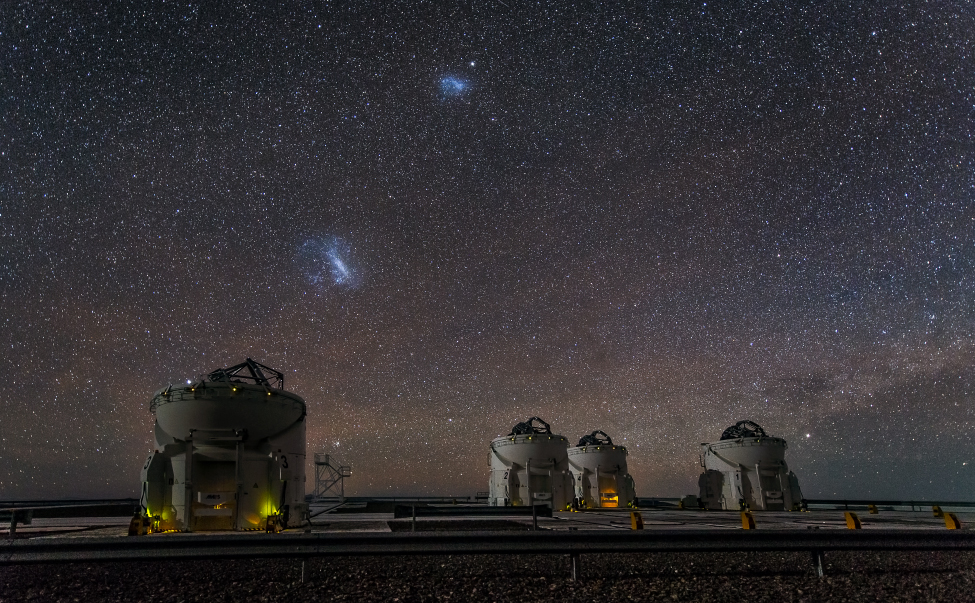 The Magellanic Clouds. The Large Magellanic Cloud is to the left of center and the SMC just above center in this image taken at Cerro Paranal in Chile. Four of the VLT's auxiliary telescopes are seen in the foreground.