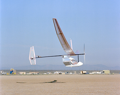 An aircraft flying in the air shown from outside, which is powered by a bicycle-type drive mechanism.