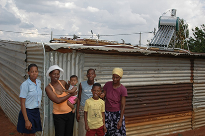 Alt text: A photo of a family of villagers in Africa in front of a solar panel on top of a roof