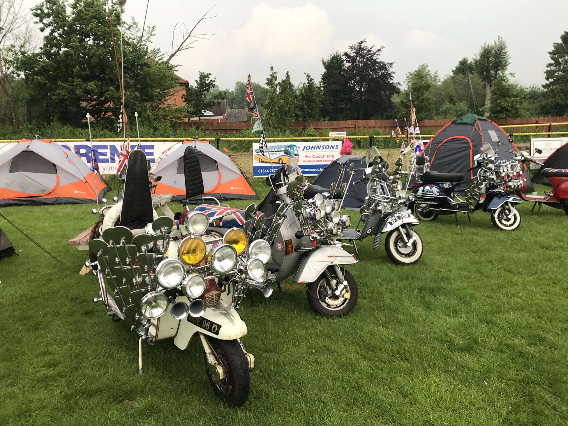 A photograph shows customized Vespa scooters parked on a grassy field with tents in the background.