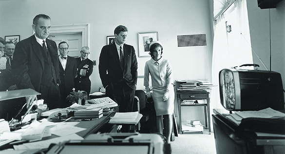 A photograph shows John F. Kennedy, Jacqueline Kennedy, Lyndon Johnson, and several others standing in a White House office, watching a small television.
