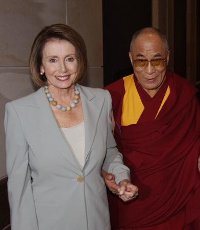 The photo shows, left, House Minority Leader Nancy Pelosi, dressed in a gray suit, holding hands with, right, Dalai Lama Tenzin Gyatso, dressed in maroon and yellow robes.