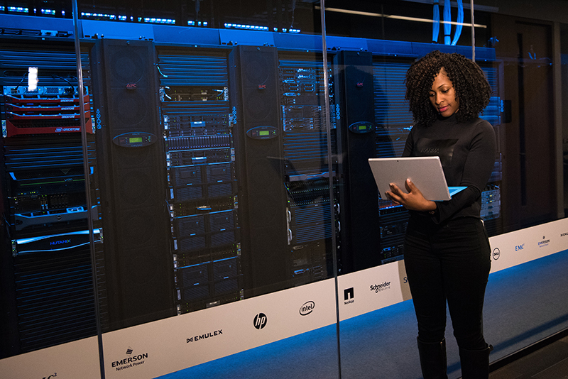 A photo shows a female data center technician working on a laptop in a server room.