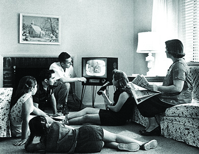 A photograph shows a man, a woman, three teenage girls, and a teenage boy sitting in a living room, watching a television.