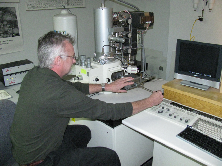 Image depicts a man using scanning electron microscope.