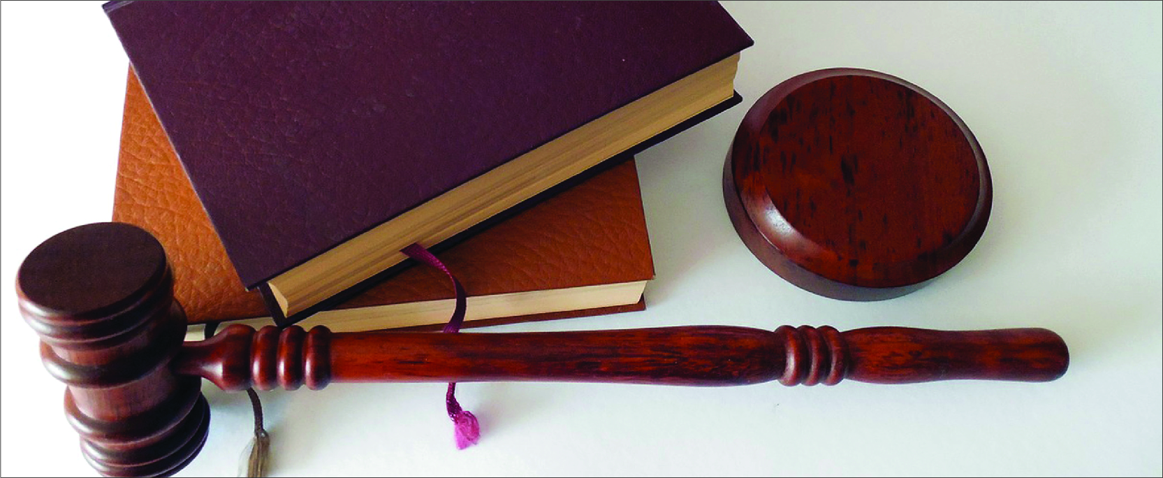 A photo of a gavel and two leather-bound books.
