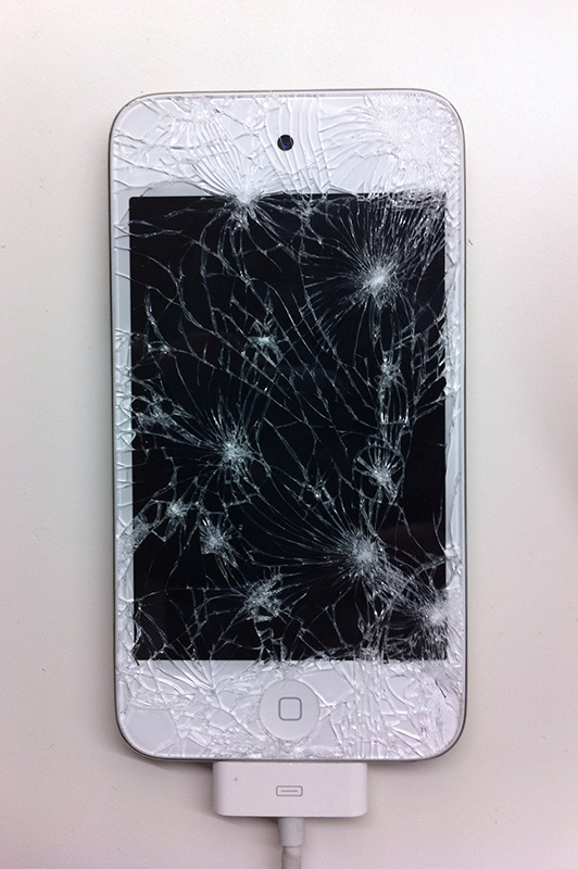 A photo shows an overhead view of an iPhone with shattered screen.