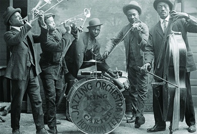 "A photograph shows a group of black jazz musicians playing their instruments. A drum reads ""Jazzing Orchestra / King and Carter / Houston Tex."""