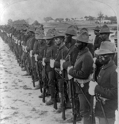 A photograph depicts a line of black soldiers in the Spanish-American War.
