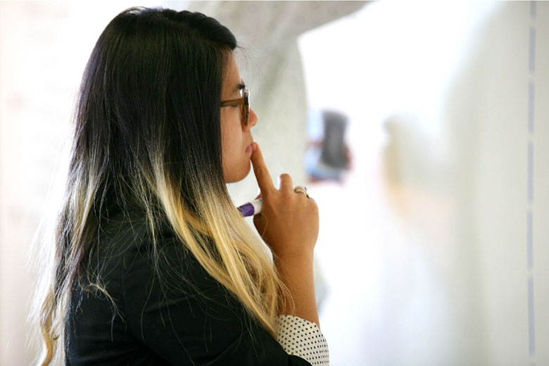 A close-up view of a person thinking, while holding a marker pen in her hand.