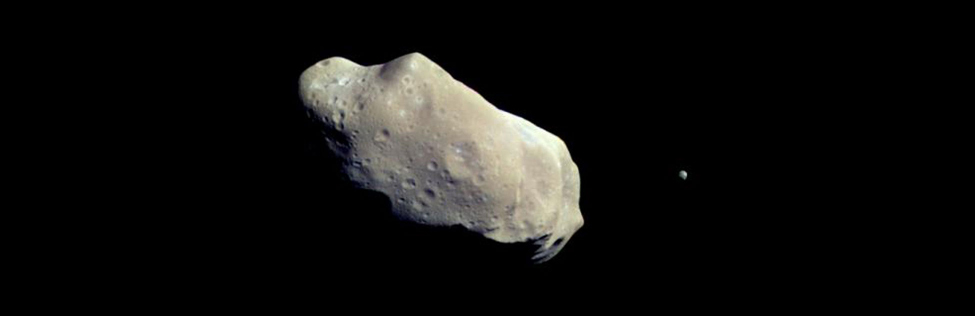 Ida and Dactyl. In this image the moon Dactyl is seen to the right of the elongated, cratered asteroid Ida.