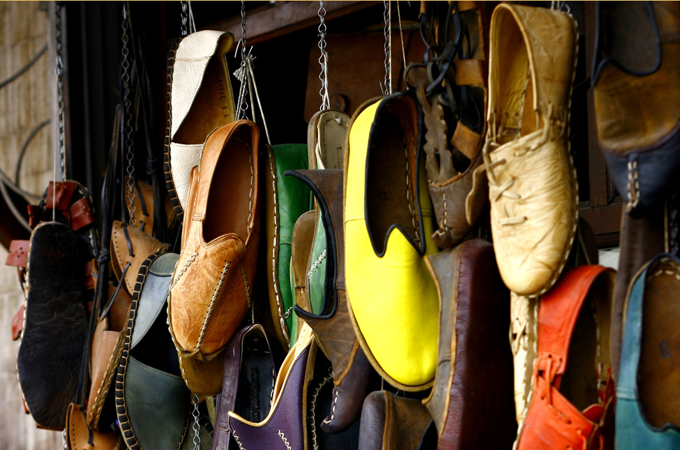 This photo shows many different pairs of shoes in various colors. The shoes appear to be hanging from a wall by cords.