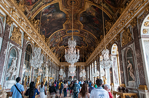 The Hall of Mirrors at Versailles features an al fresco and gilded domed ceiling; many large, hanging crystal chandeliers; exquisite painted panels on the walls; and mirrors—lots and lots of mirrors—to give an illusion of space. Tourists are pictured roaming the Hall.