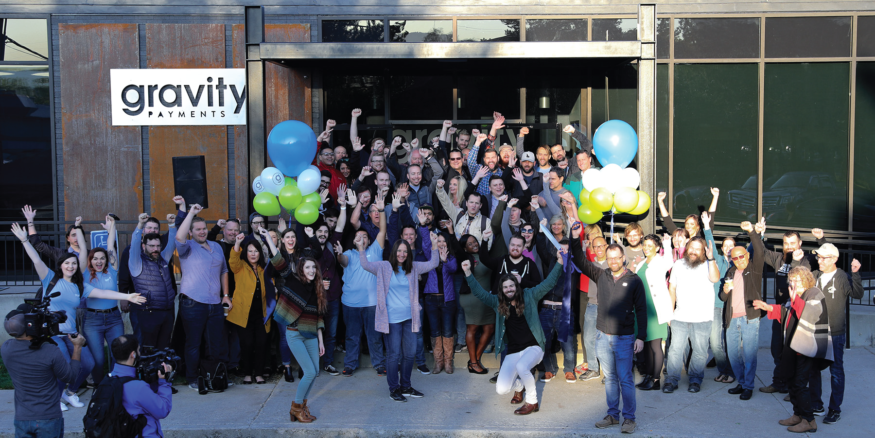 Photo of a crowd of people in front of a Gravity Payments banner.