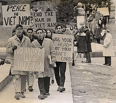 "A photograph shows students protesting on the University of Madison-Wisconsin campus. They hold signs reading ""No more war in Viet Nam""; ""Peace in Viet Nam""; ""End the war in Viet Nam""; and ""Use your head—not your draft card."""