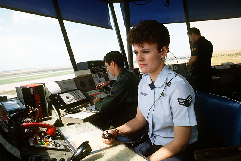 A photo shows air traffic controllers of the Air Force Communications Command working in the base control tower while observing incoming and outgoing aircraft.