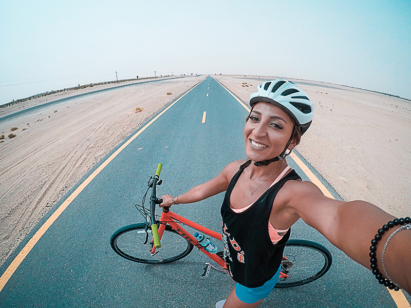 A photo shows a female cyclist in a bike helmet holding a bicycle in an empty road while smiling for a selfie.